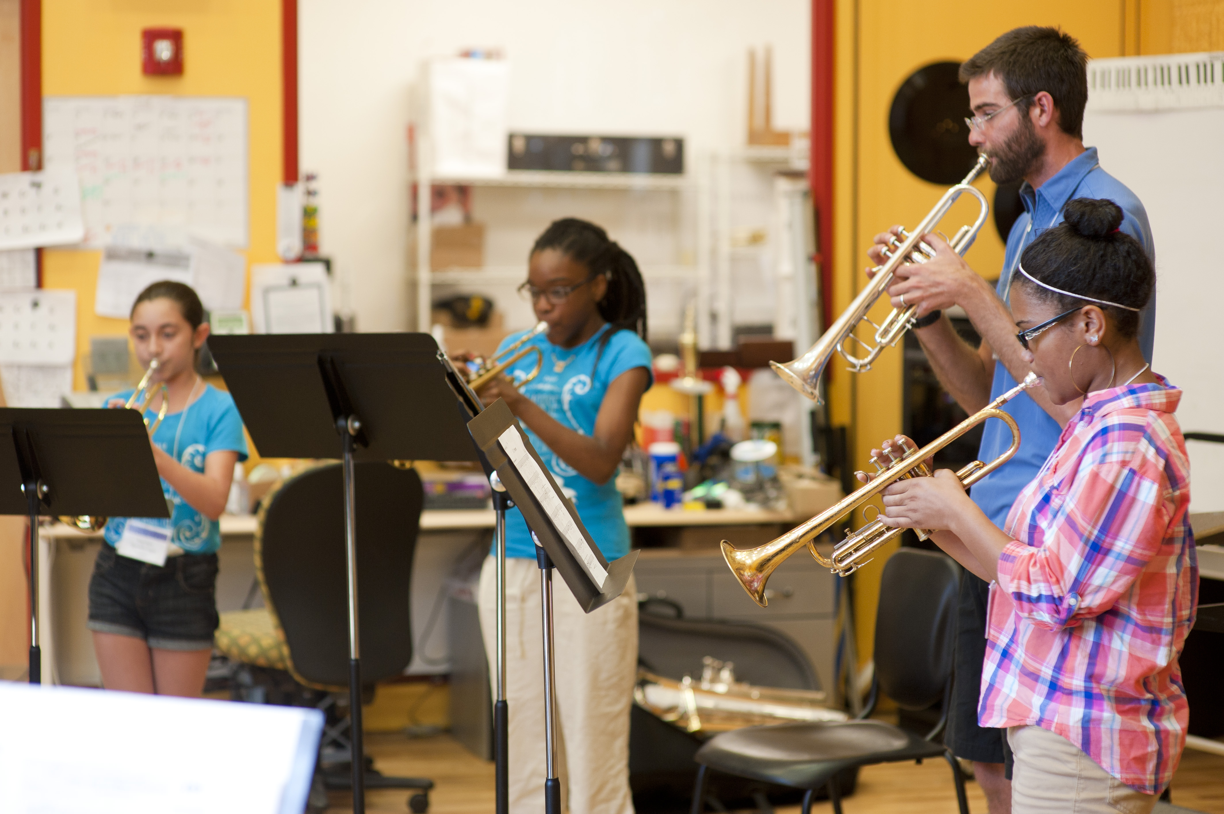 Teaching Artist playing trumpet with NHPS students