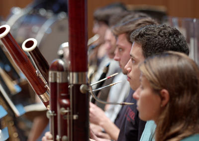 Students playing bassoons in an orchestra rehearsal.